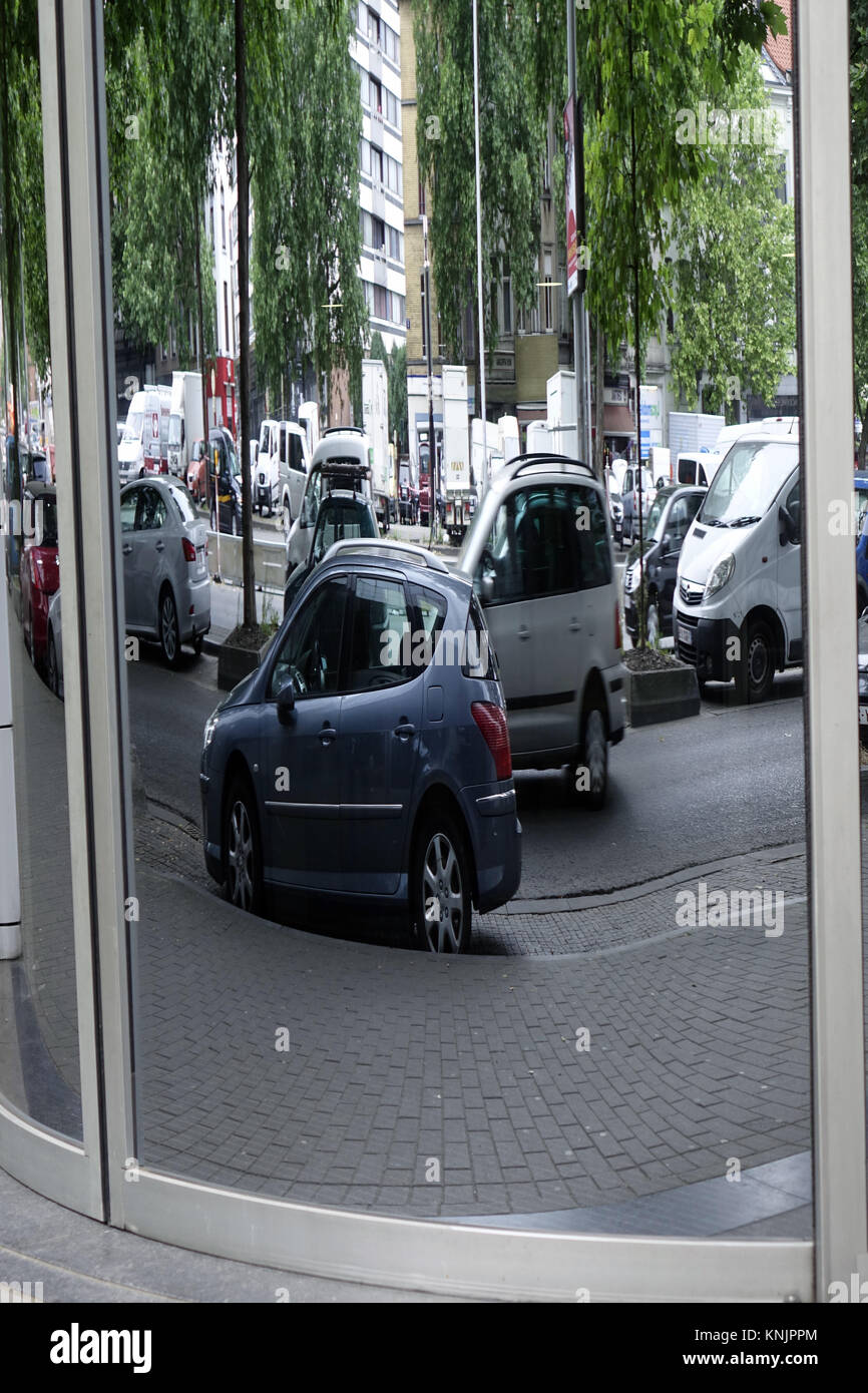 Brussels, Belgium. 24th June, 2017. Travelling and parked cars are reflected in a distorted way in the round glass pane of a building, in the Belgian capital Brussels, pictured on 24.06.2017. - NO WIRE SERVICE - Credit: Sascha Steinach/dpa-Zentralbild/dpa | usage worldwide/dpa/Alamy Live News Stock Photo