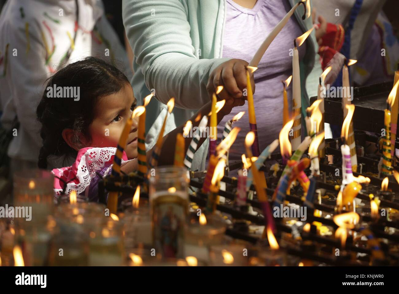 San Salvador, El Salvador. 12th Dec, 2017. Pilgrims light candles in honor of the Virgin of Guadalupe in San Salvador, Stock Photo
