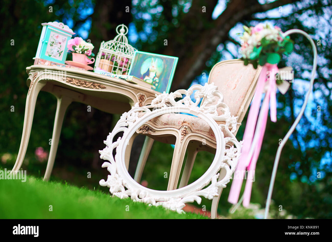 Retro styled chair, table and white carved frame. Pretty things, symbols of Alice in Wonderland - Stock Image