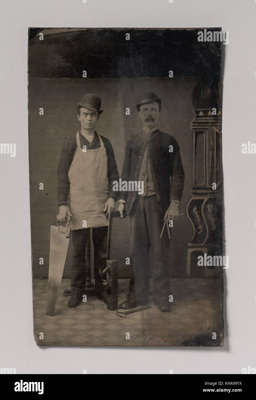 [Two Carpenters with a Handsaw, Wood Plane, Hammer, Compass, and Square]. Artist: Unknown (American); Date: 1880s; Stock Photo