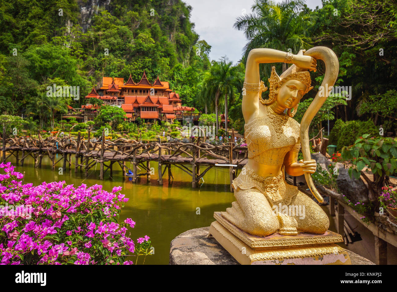 Thai literature Goddess of the earth statue twisting her hair in front of Thailand rural Buddhist temple. - Stock Image