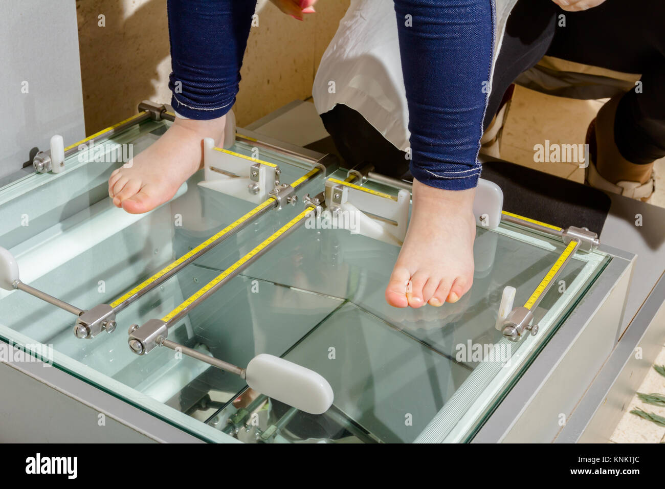Doctor orthopedist is measuring child's foot with adjustable metal rulers. - Stock Image