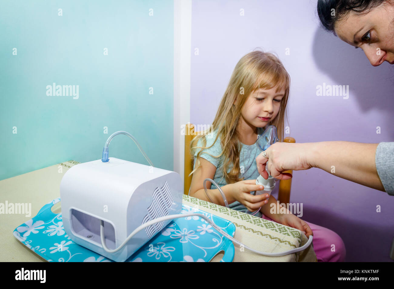 Woman is preparing inhalation treatment for child with asthmatic problems. - Stock Image