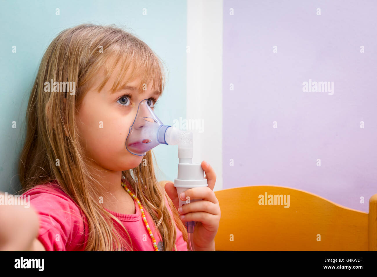 Child with asthmatic problems is take inhalation with mask on her face. - Stock Image