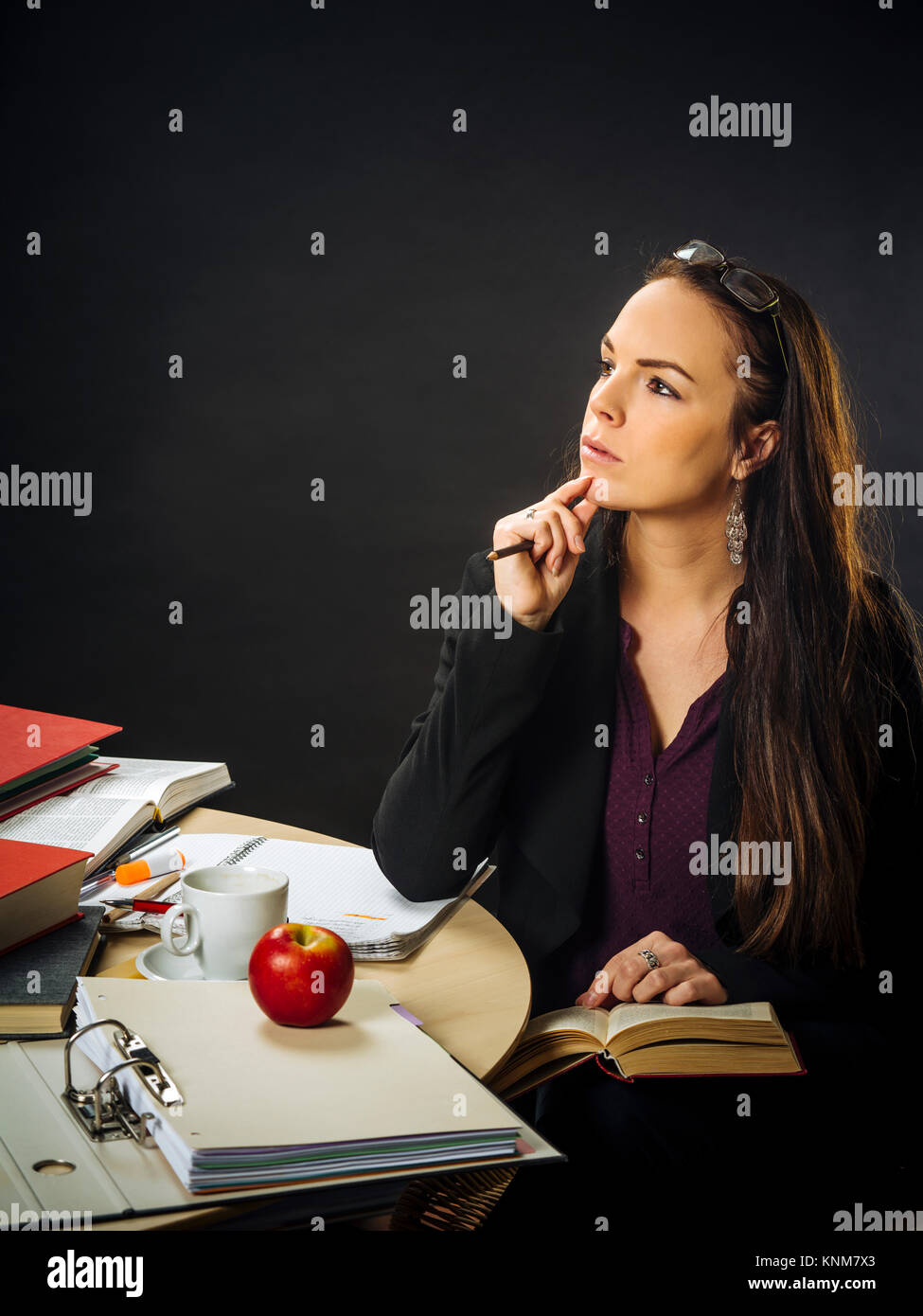 Photo of a teacher in her 30's sitting at a messy desk in front of a large blackboard reading a book. - Stock Image
