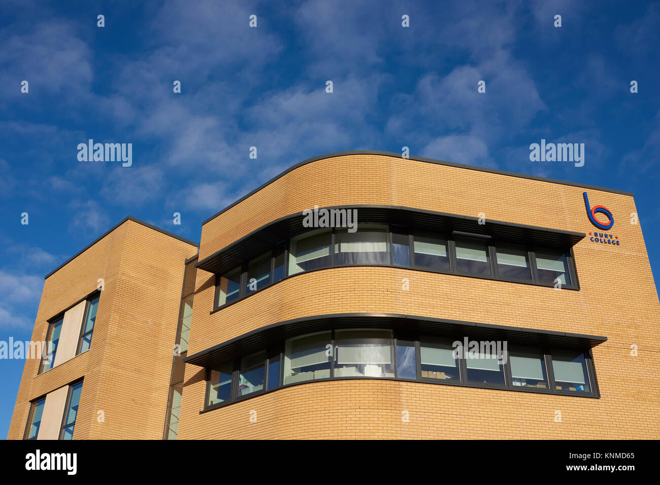 Sun shining on curved ribbon windows with solar shading or Brise Soleil in curved modern building facade in bury - Stock Image