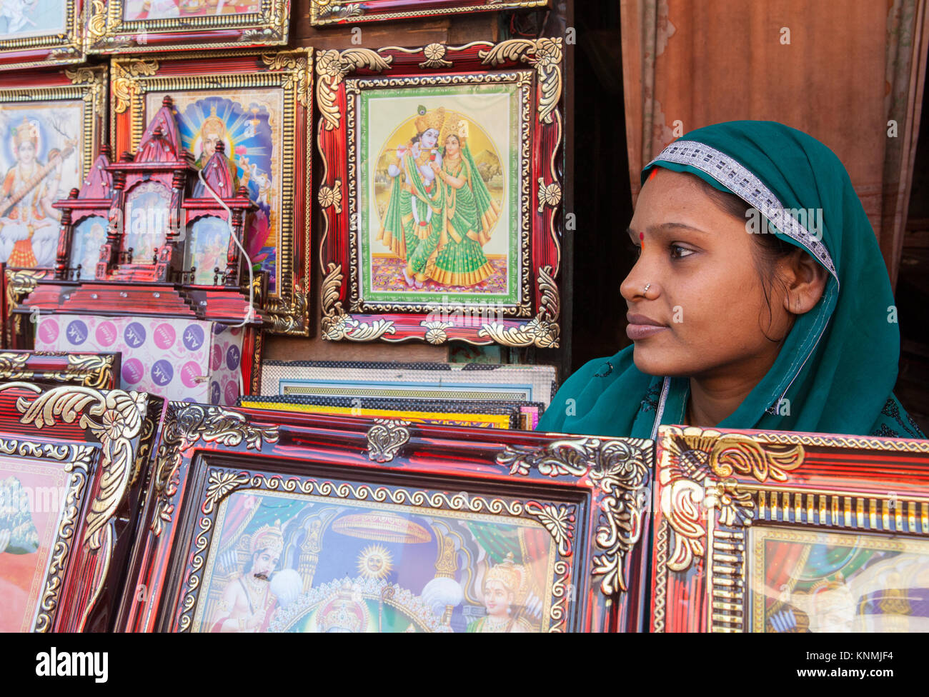 Portrait of a woman selling images of Hindu gods at street stall in the bazaar at Ayodhya, India - Stock Image
