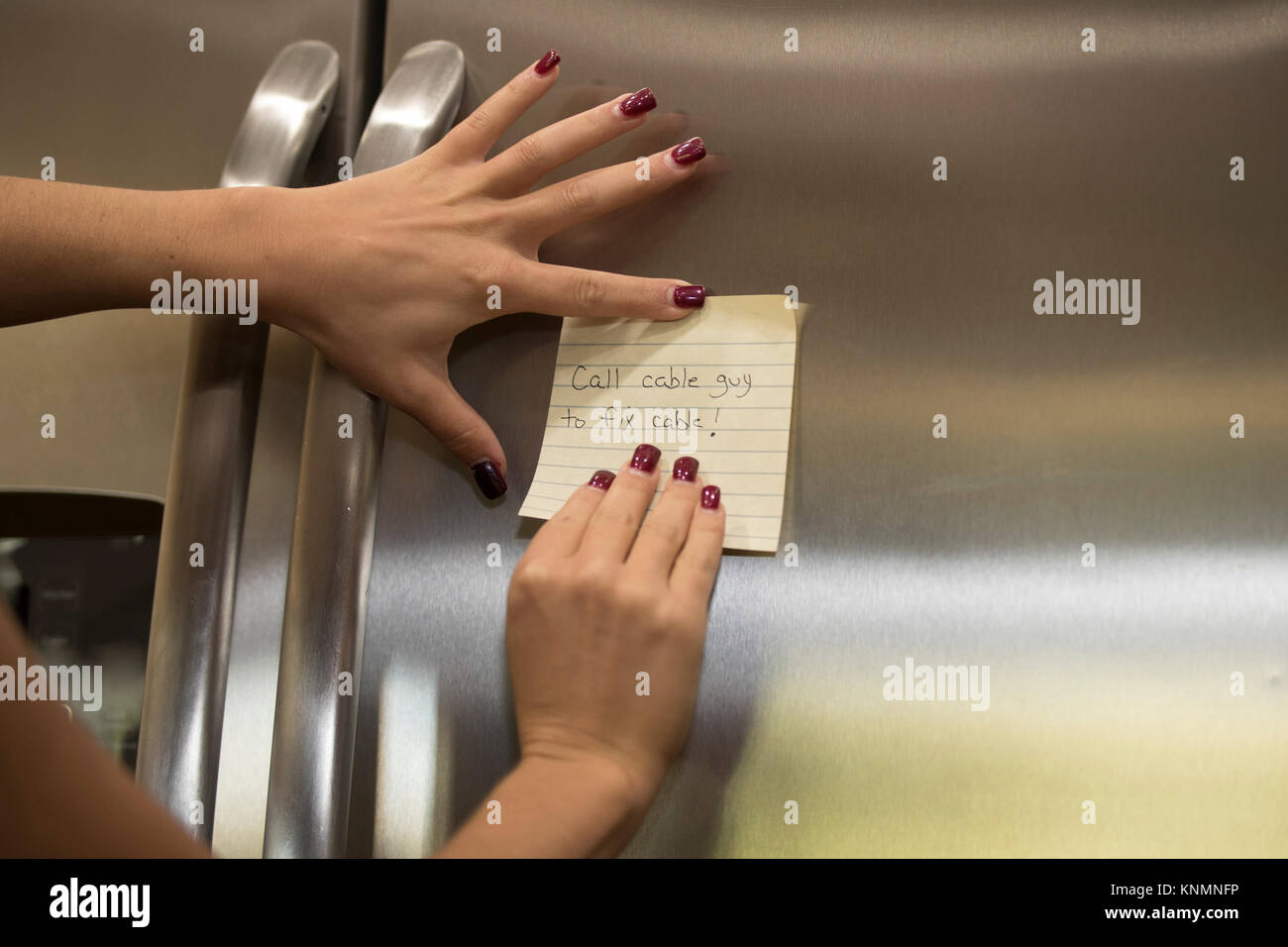 Sticky note reminders stuck on the refrigerator in the kitchen. - Stock Image