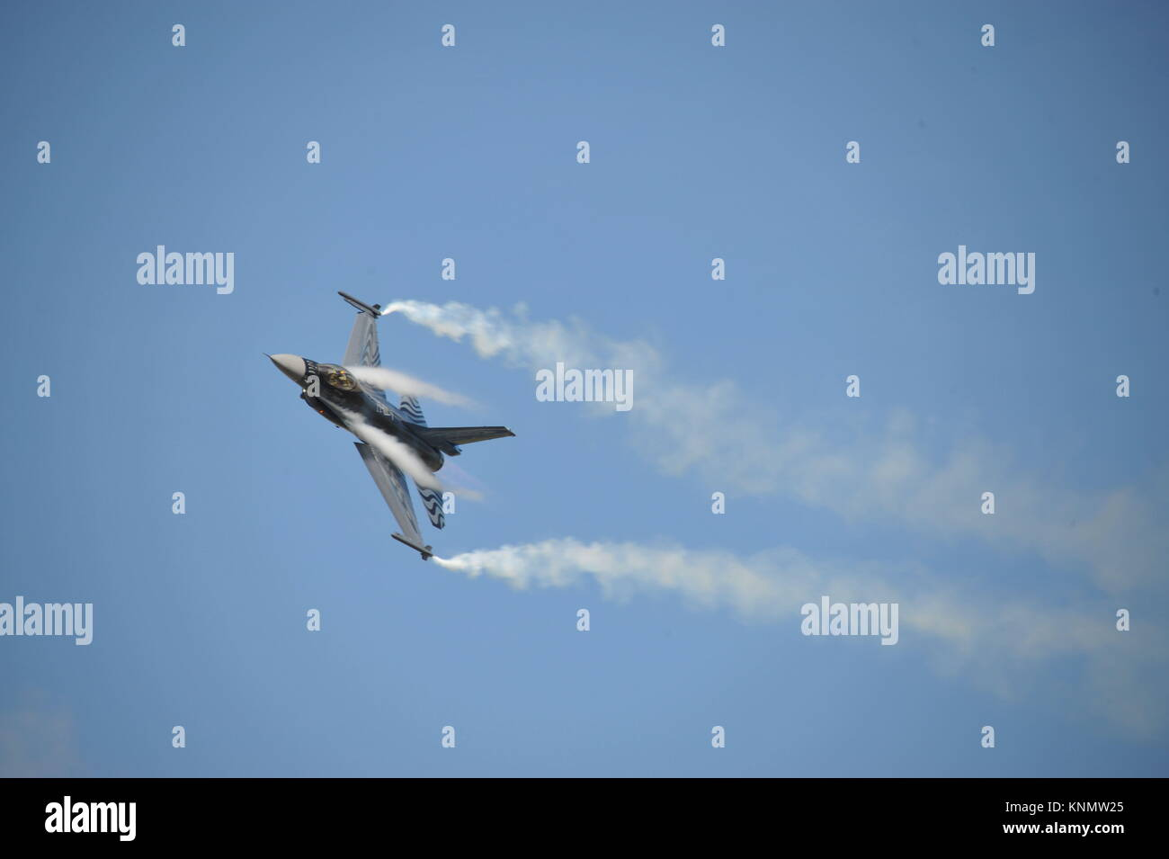 Lockheed Martin General Dynamics f-16 fighting falcon from Belgium during an airshow with condensation going over - Stock Image