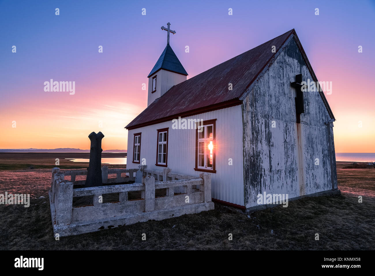 Sun shines through church at sunset in Iceland Stock Photo