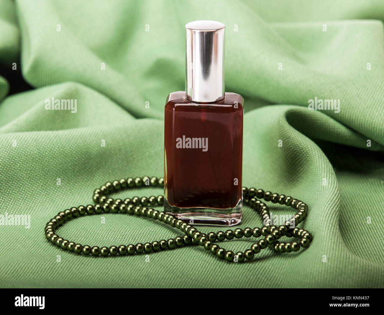 An oil glass bottle full of dark red oil on a green fabric with a