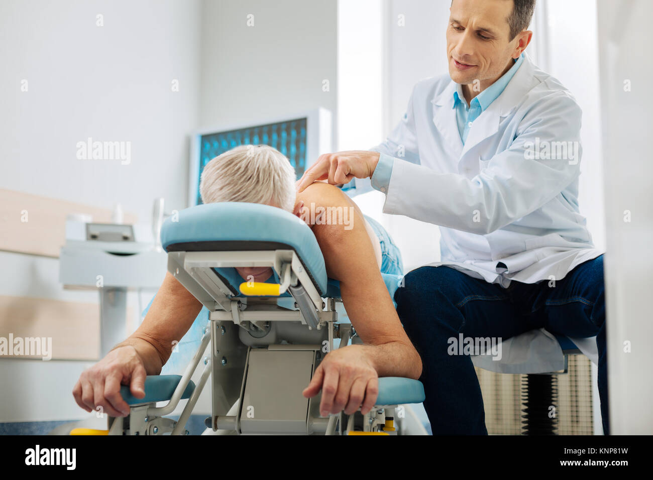 Professional male doctor treating his patient - Stock Image