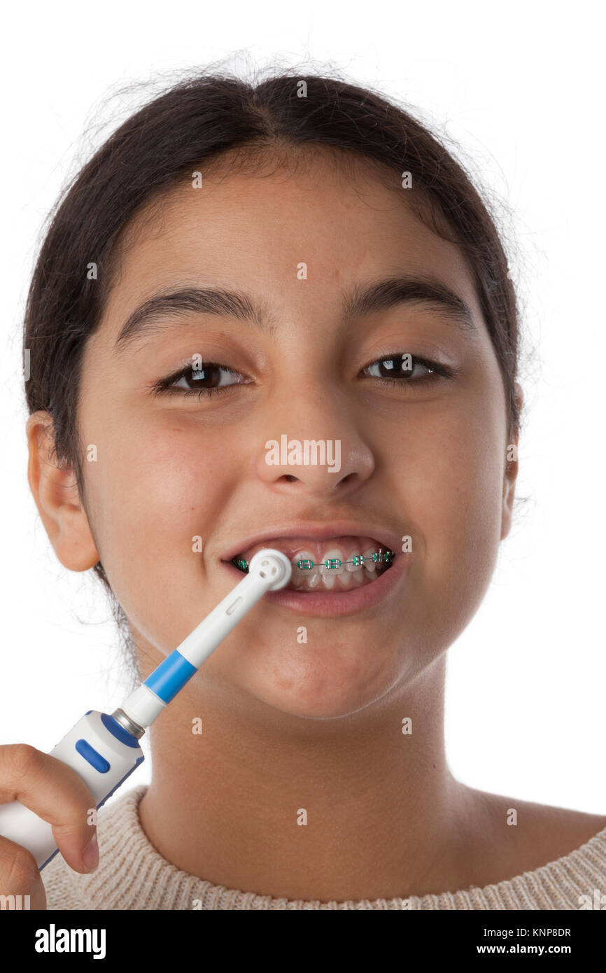 Teenage girl is brushing her teeth with dental braces with an electric tooth brush - Stock Image