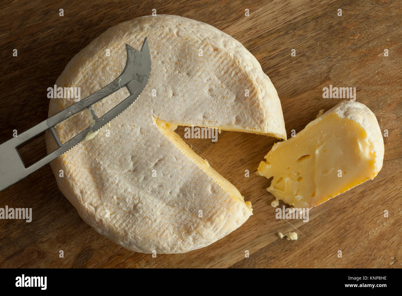 Reblochon de Savoie cheese from raw cows milk with a slice - Stock Image
