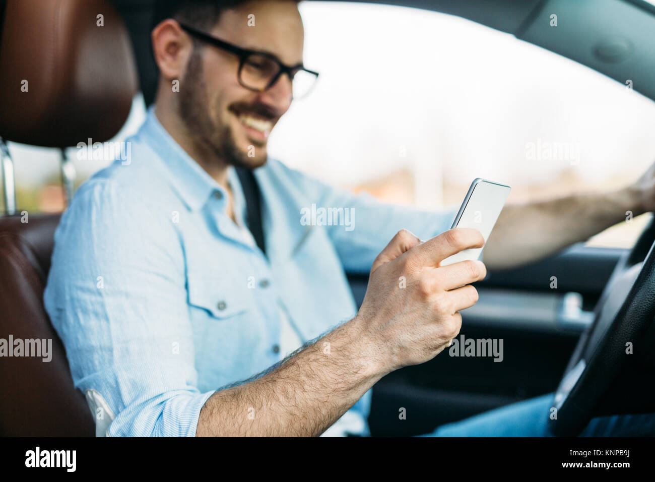 man using phone while driving the car - Stock Image