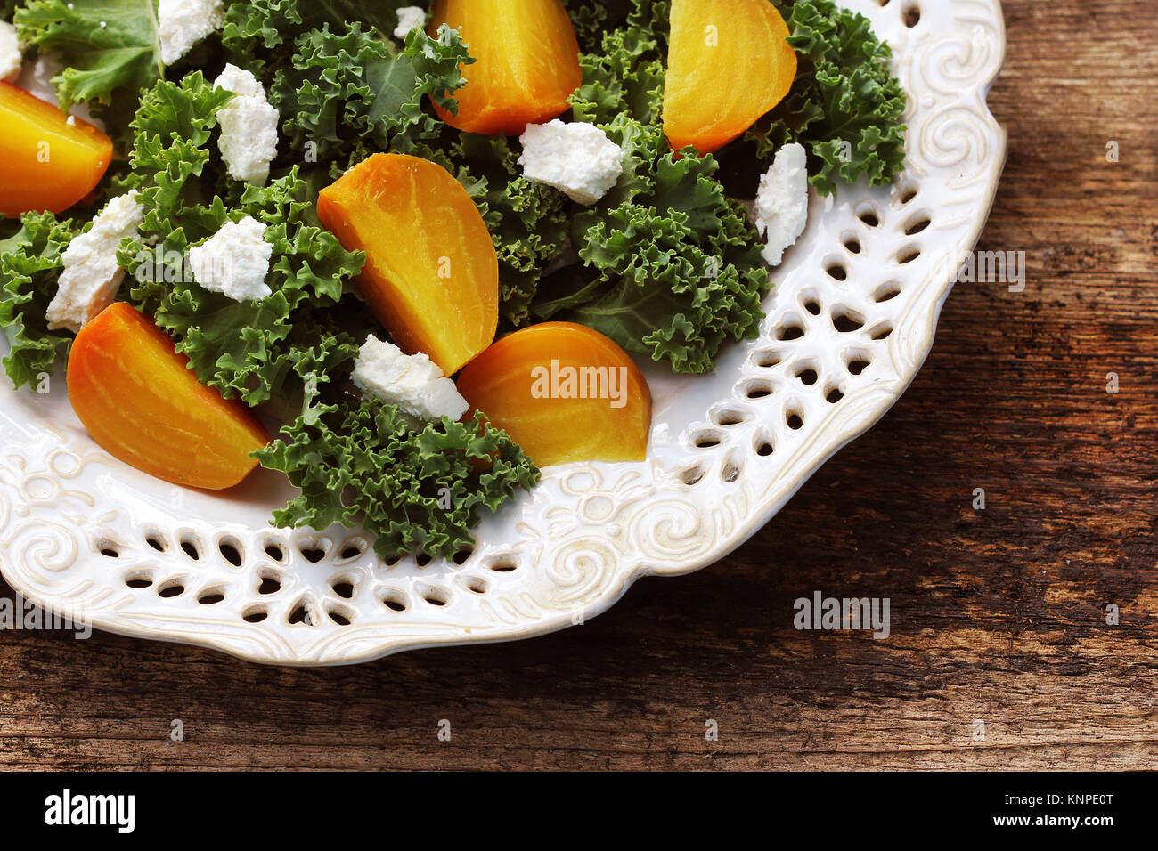 Golden beet salad with fresh kale lettuce, feta cheese on wooden background - Stock Image