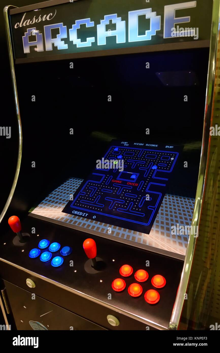 A classic arcade game with a Pac Man game showing on the screen. - Stock Image
