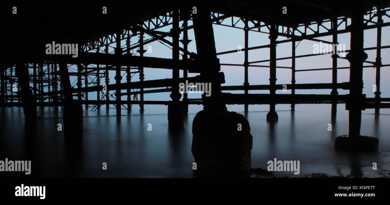 Silhouetted long exposure in to the light underneath Hastings Pier. - Stock Image