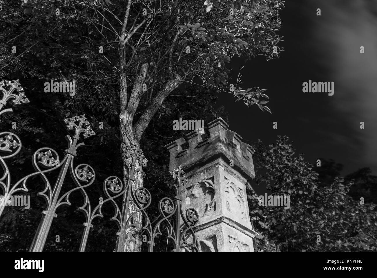 Night shot of an old metal fence and stone tower - Stock Image