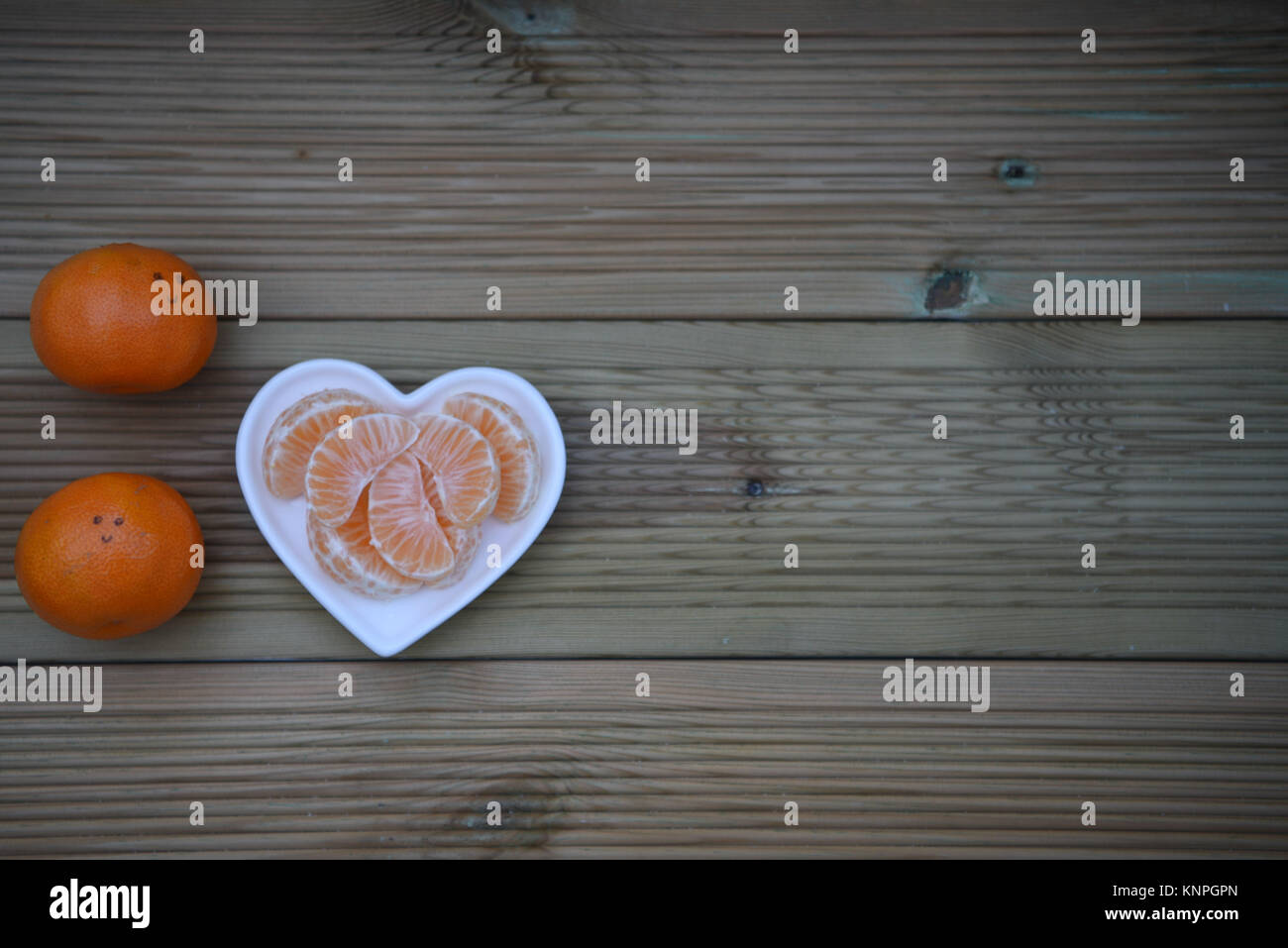 color food photography image of healthy oranges fruit in love heart shape white dish and happy smile drawn on the Stock Photo