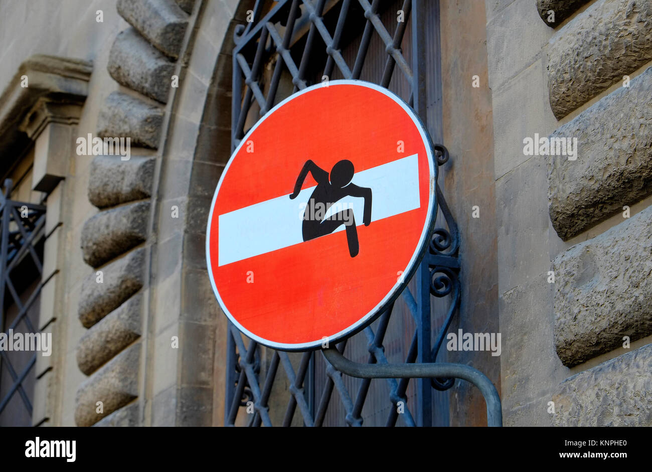 red no entry sign with graphic illustration of man climbing through horizontal white rectangular box - Stock Image