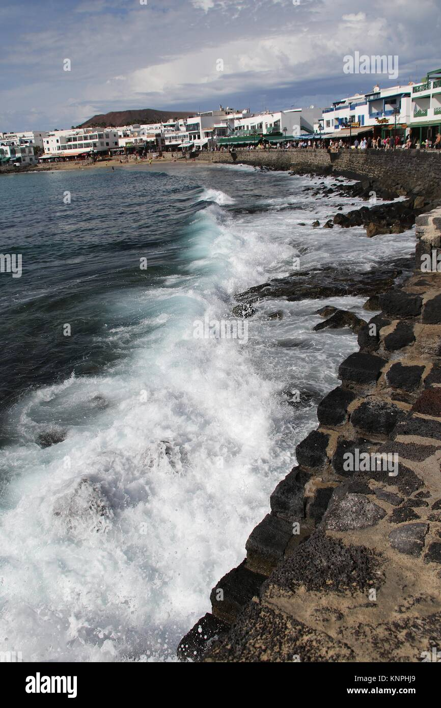 waves lapping against a seawall at Playa Blanca, Lanzarote - Stock Image