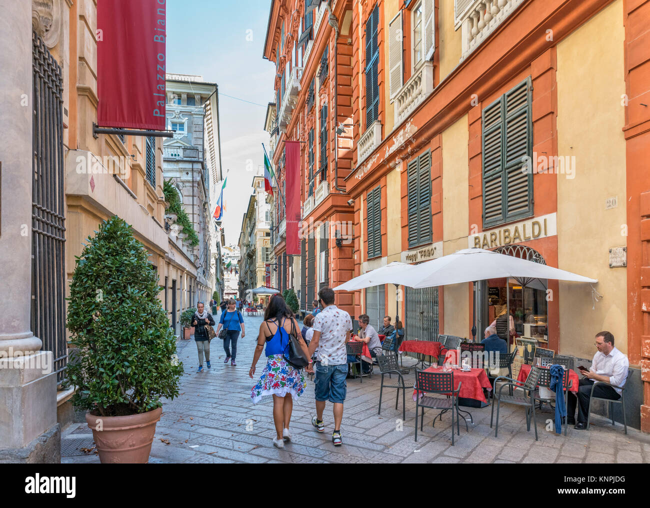 Sidewalk cafe on Via Garibaldi in the old town, with the Palazzo Bianco to the left, Genoa, Liguria, Italy - Stock Image