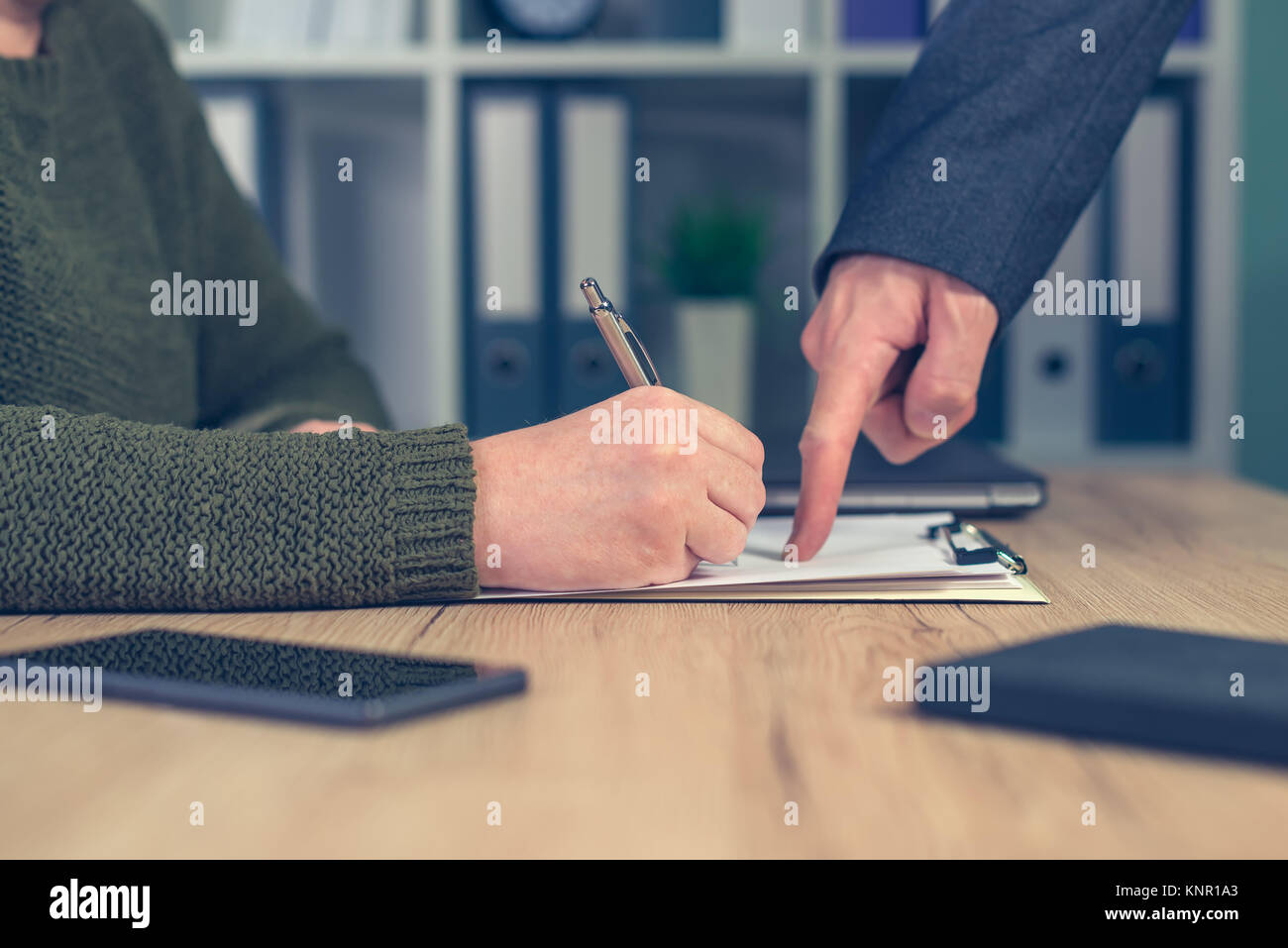 Boss giving orders and work tasks with assignment to be improved. Male hand pointing to female employee's paperwork. - Stock Image