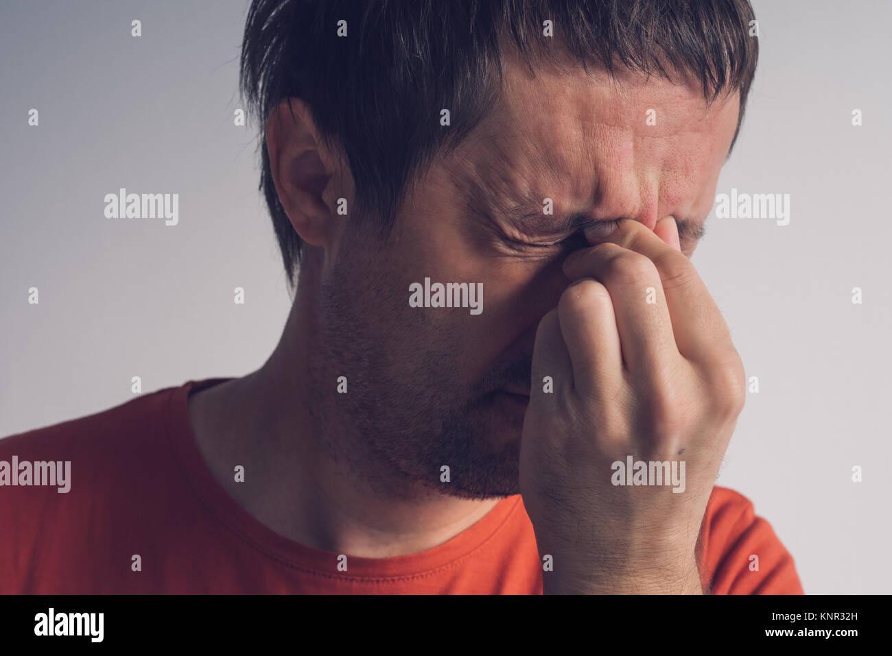 Man with migraine headache, adult caucasian male suffering from severe pain in head. - Stock Image