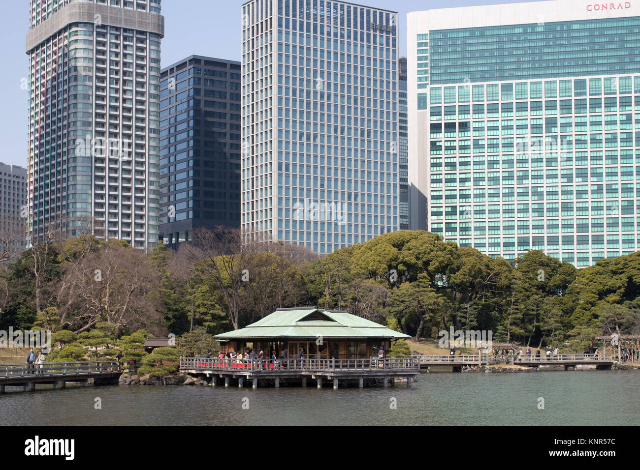 A traditional Japanese tea house in the Hamarikyu Gardens surrounded by City skyscrapers, a public park in Chūō, - Stock Image
