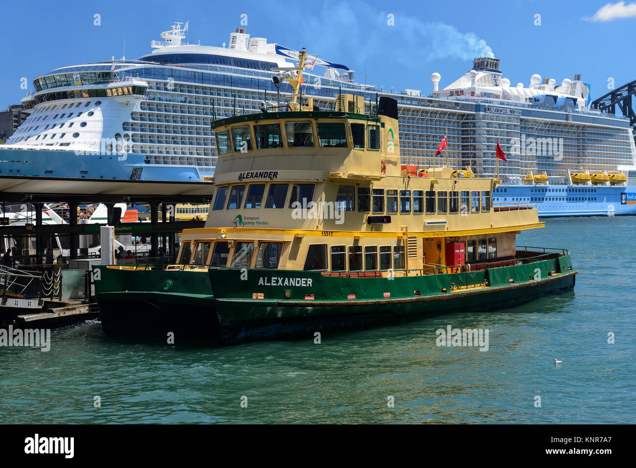Ferry boat arriving at Circular Quay, with cruise ship berthed at Overseas Passenger Terminal in background - Sydney, - Stock Image