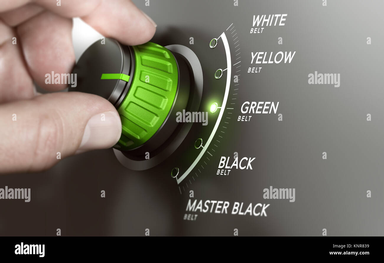 Hand turning a knob over grey background and selecting the green belt level. Lean management training concept. Composite - Stock Image
