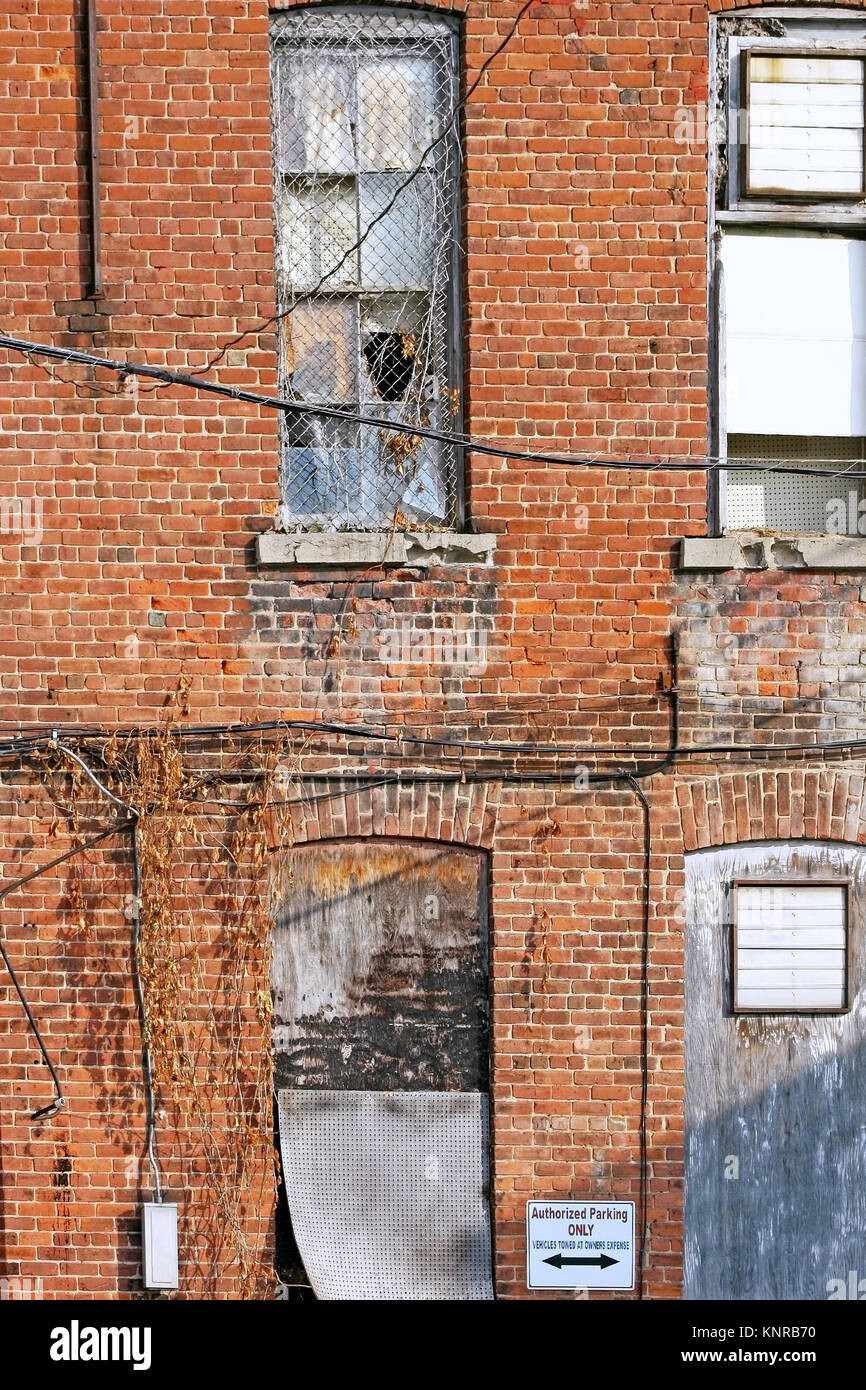 Run down building exterior with old broken windows - Stock Image