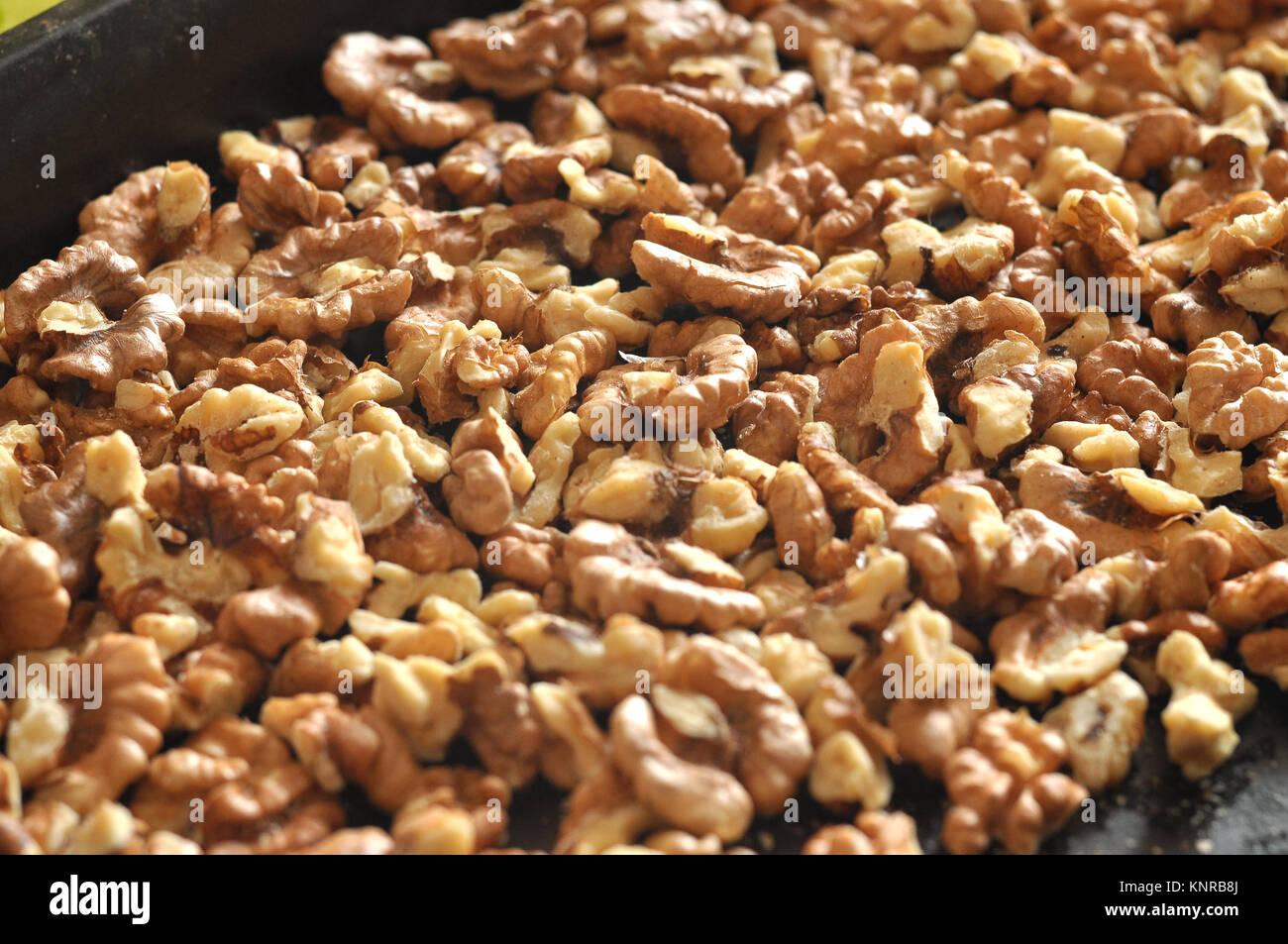 Baked walnut kernels on a black backing tray close-up. Walnut background. - Stock Image