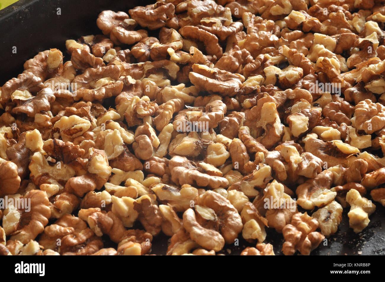 Baked walnut kernels on a black backing tray close-up. Walnut background - Stock Image