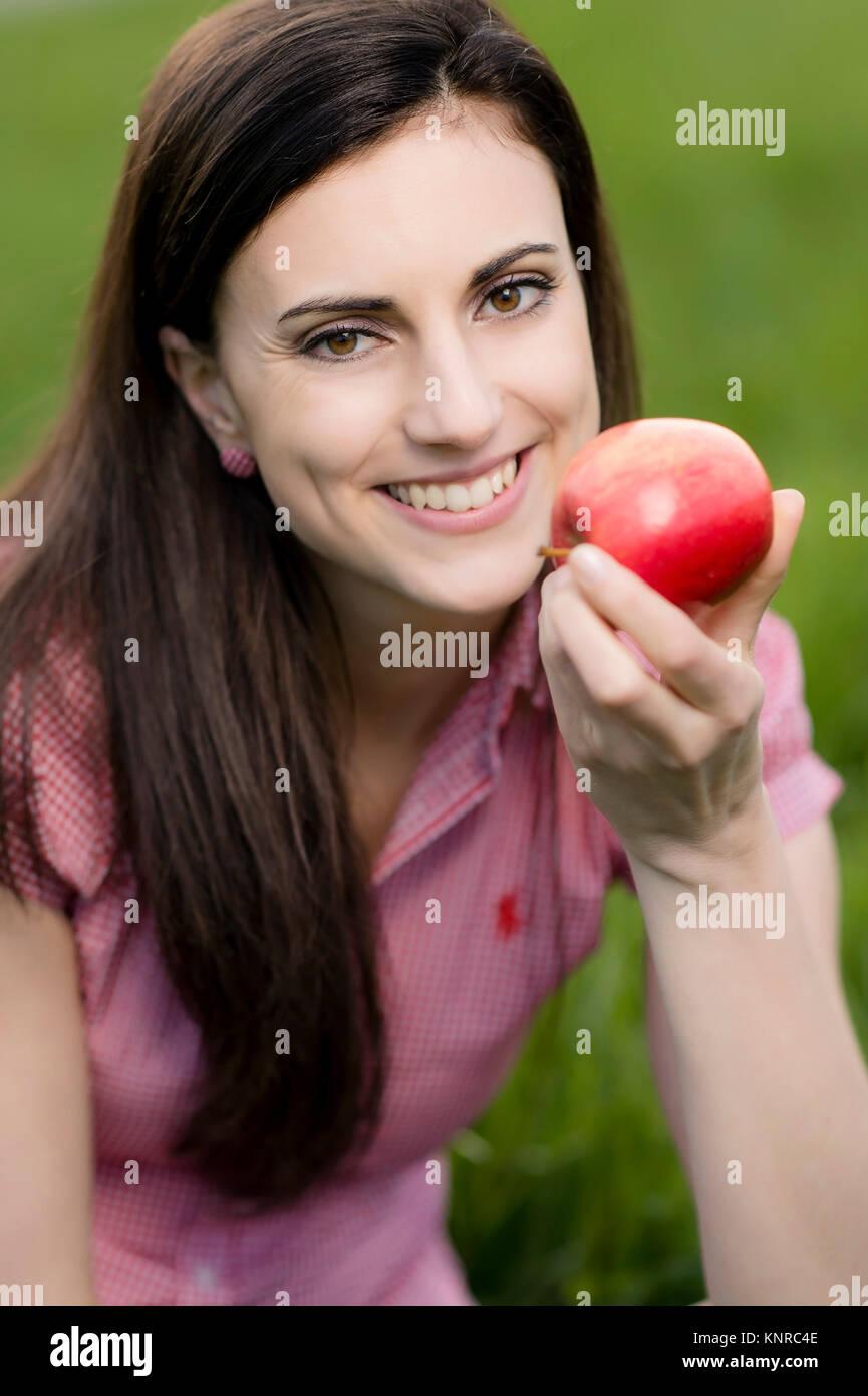 Junge Frau mit Apfel in der Wiese - woman with apple in meadow Stock Photo