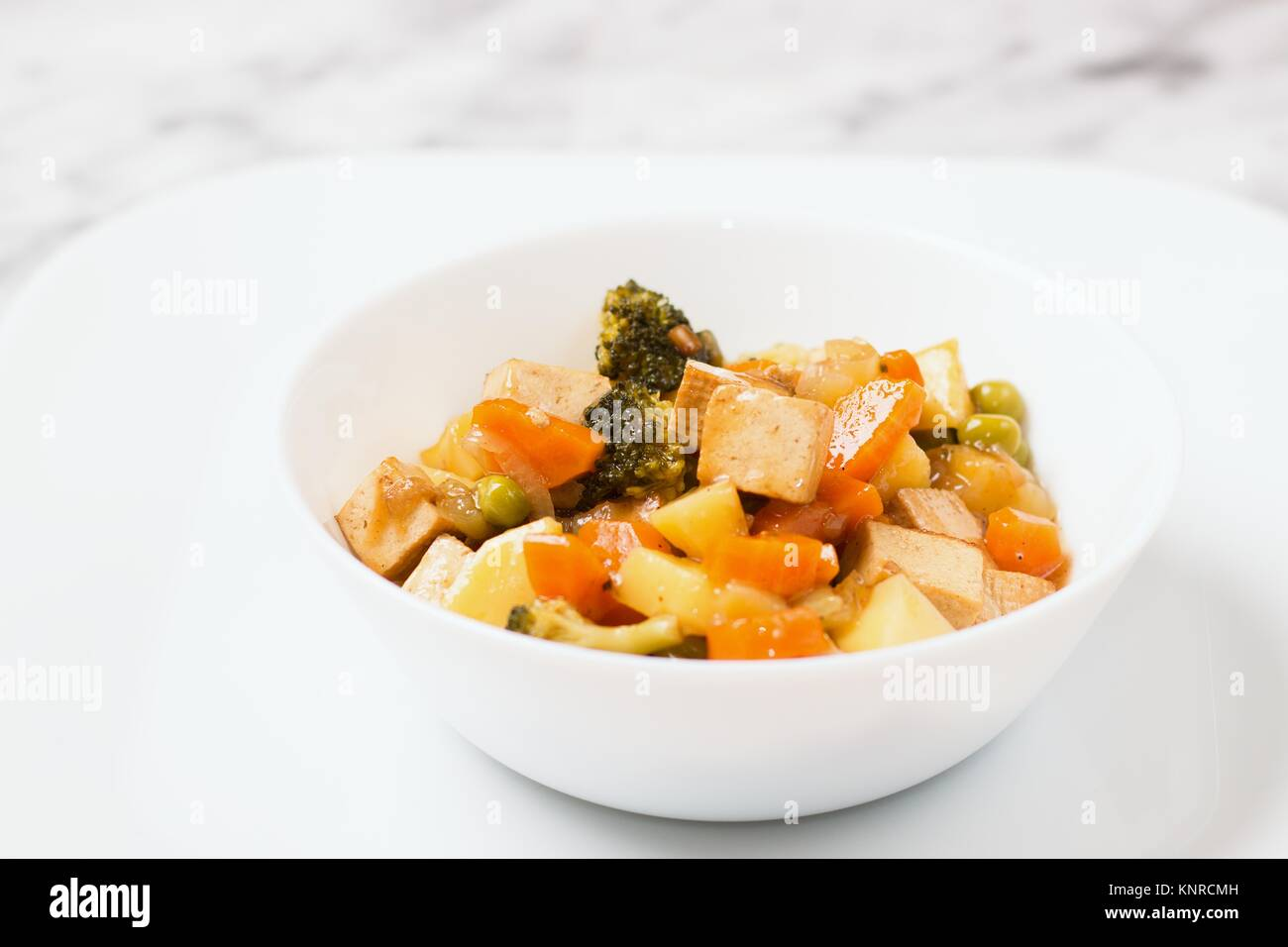 White bowl of asian style vegan meal of smoked tofu and cooked vegetables - Stock Image