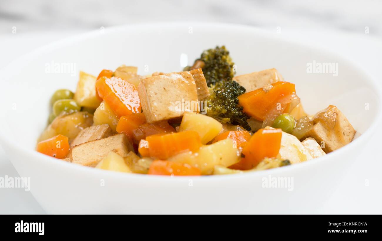 Wide screen shot of healthy vegan dish made of tofu,carrot,broccoli and potatoes - Stock Image