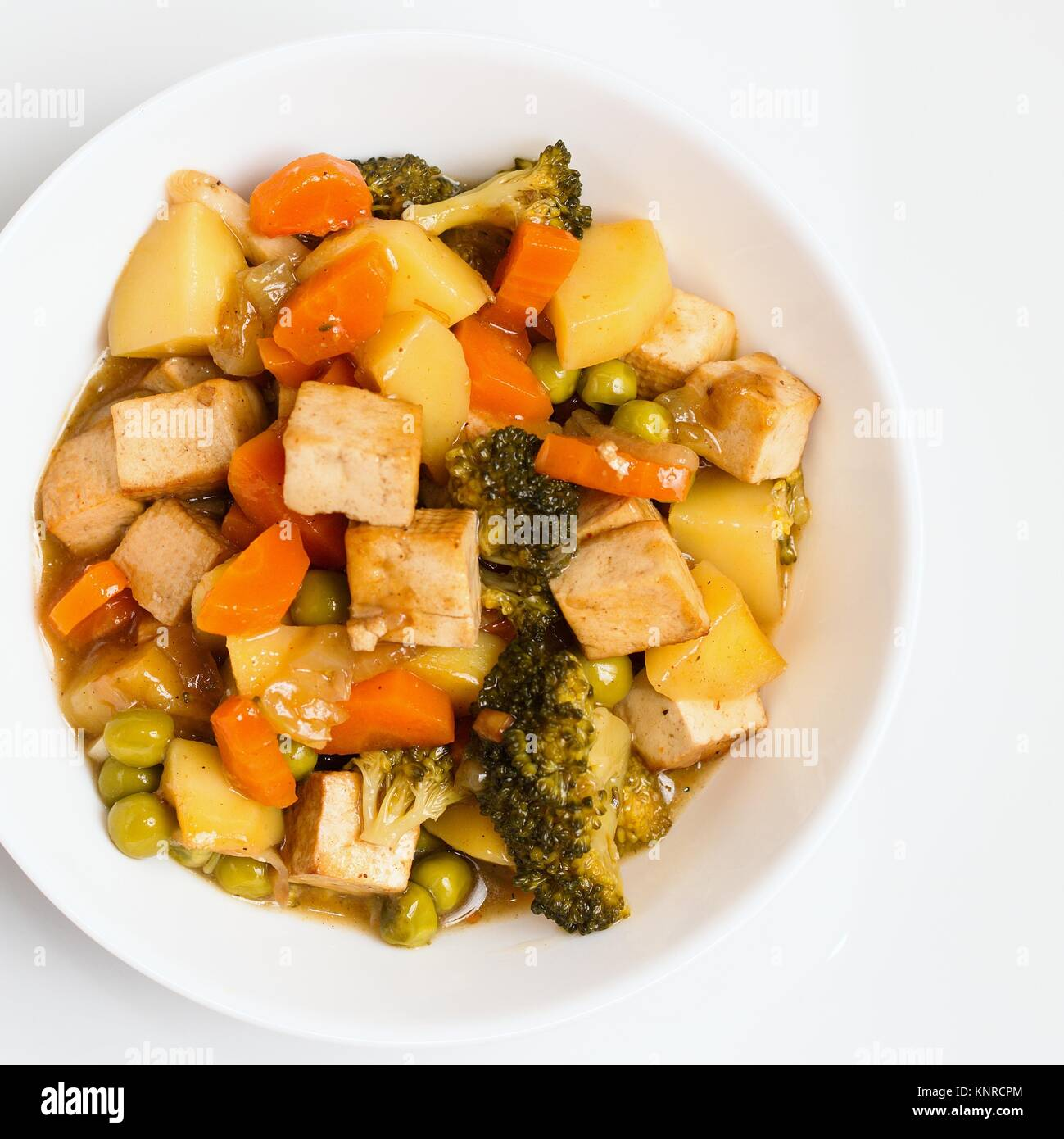 Cooked vegetables with tofu in white bowl. Top down view on the dish - Stock Image