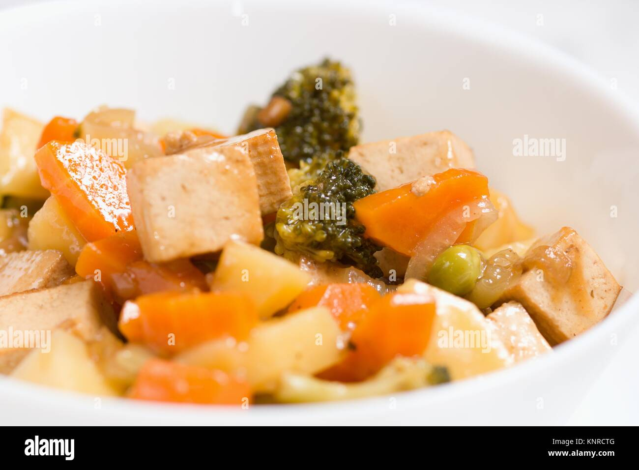 Macro shot of served vegan meal of tofu and several cooked vegetables in white bowl - Stock Image