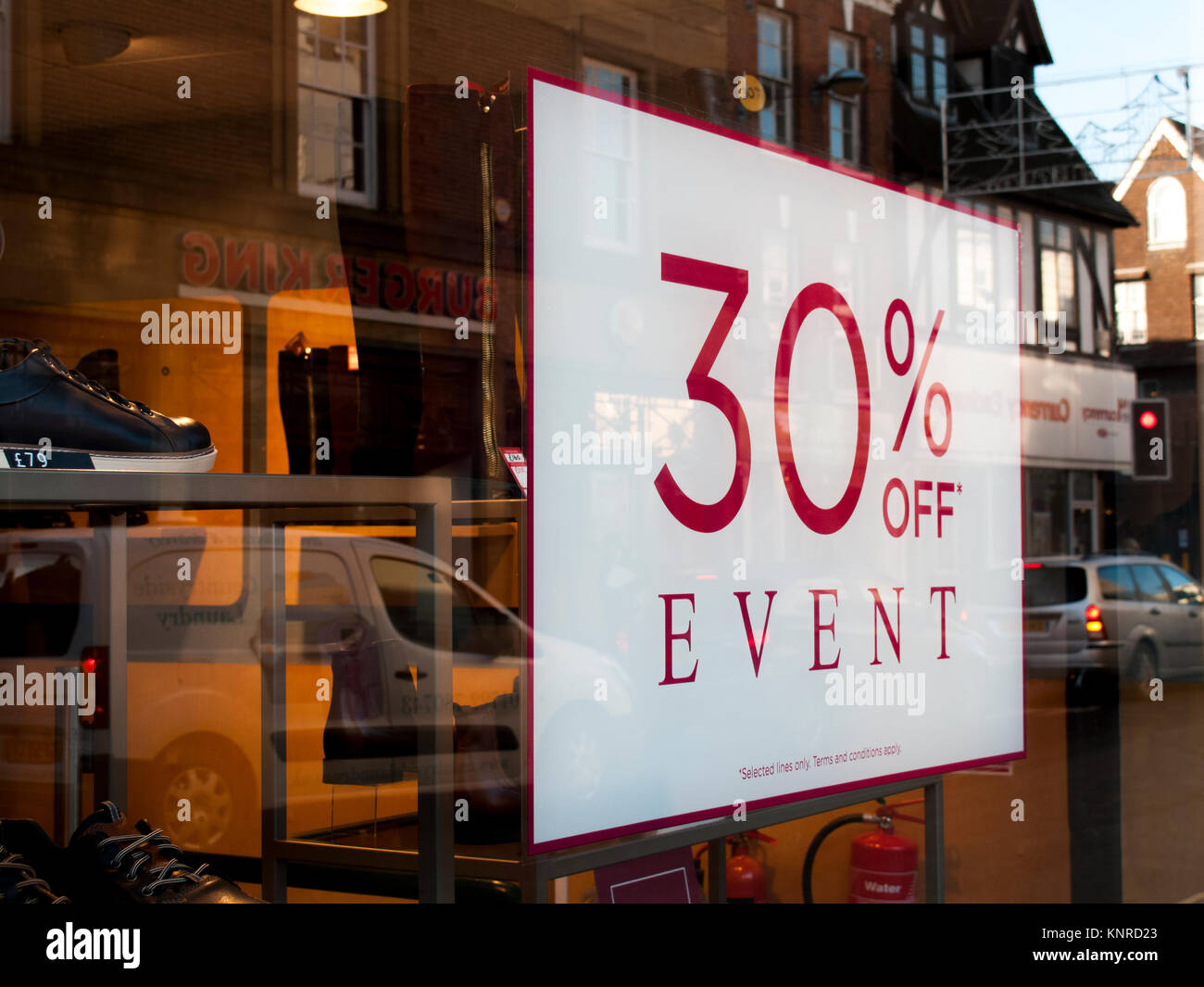 30 percent event sign advertising price discounts in shoe shop window - Stock Image