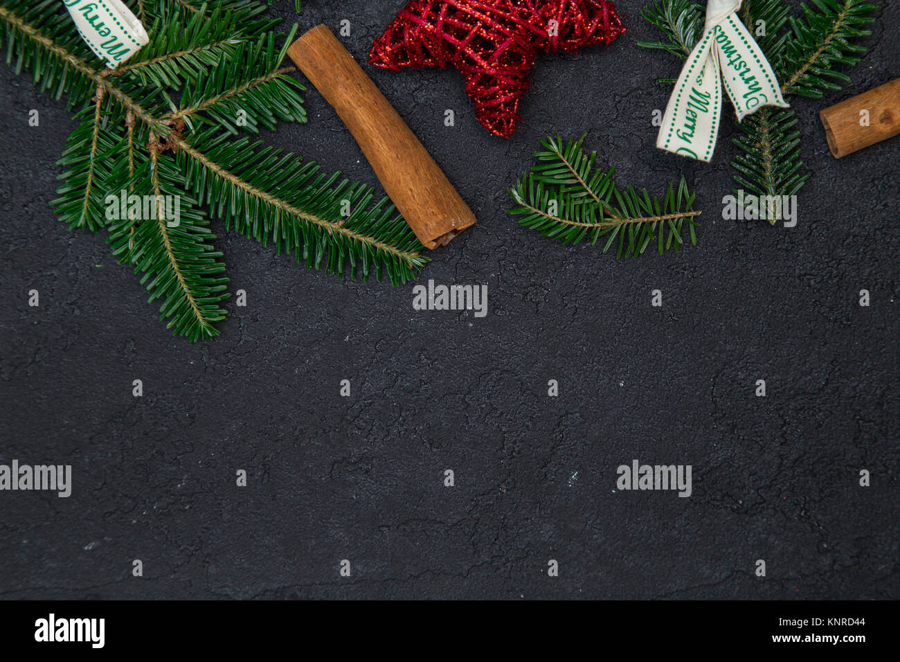 black concrete christmas or new year background with a top border of sruce branches white bows red stars and cinnamon sticks space for your text or