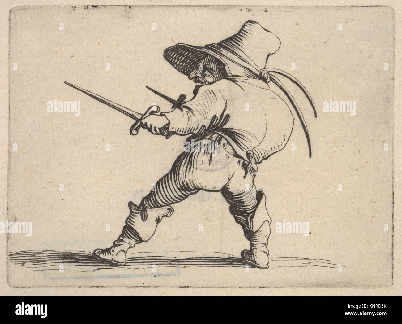 Small male figure wearing a hat, with daggers in both hands, and placing his weight on his right foot as he stretches - Stock Image