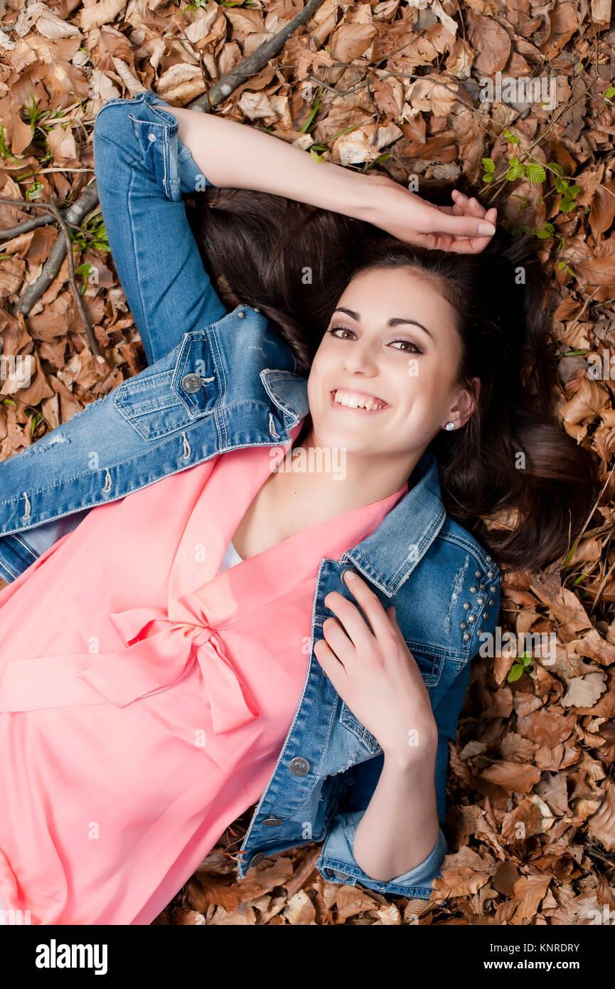 Junge Frau liegt im Laub - woman lying in leaves - Stock Image