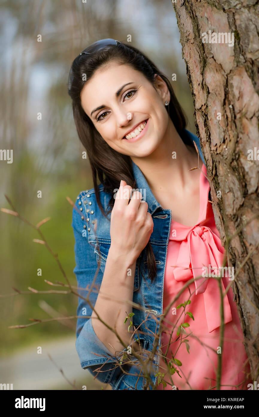 Junge Frau steht neben Baumstamm - woman is standing next to tree trunk - Stock Image