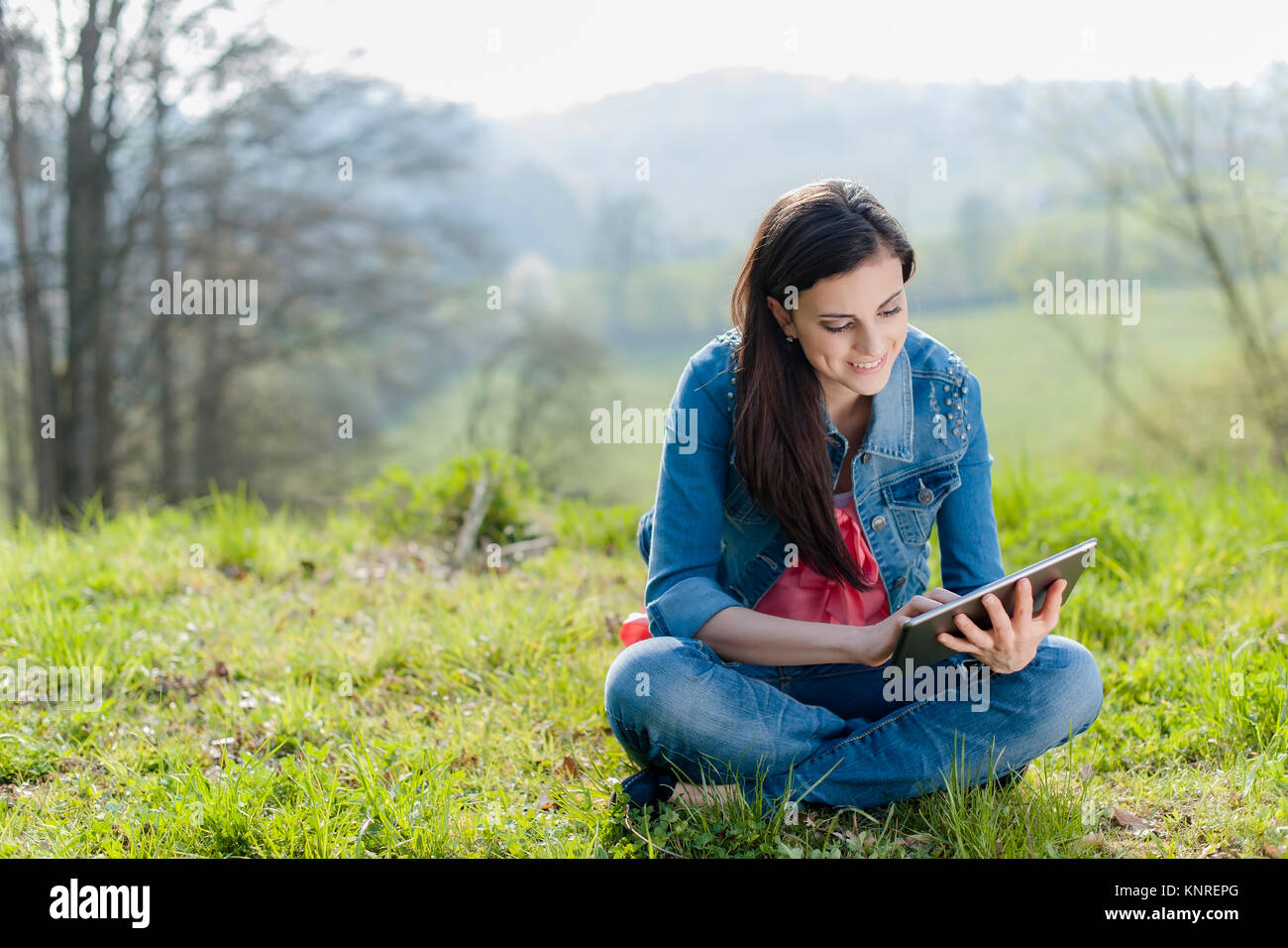 Junge Frau mit IPad sitzt in der Wiese - woman with Ipad - Stock Image
