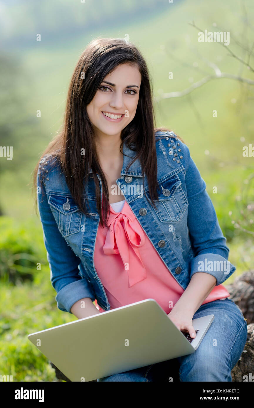 Junge Frau sitzt mit Laptop in der Natur - woman with laptop in nature Stock Photo
