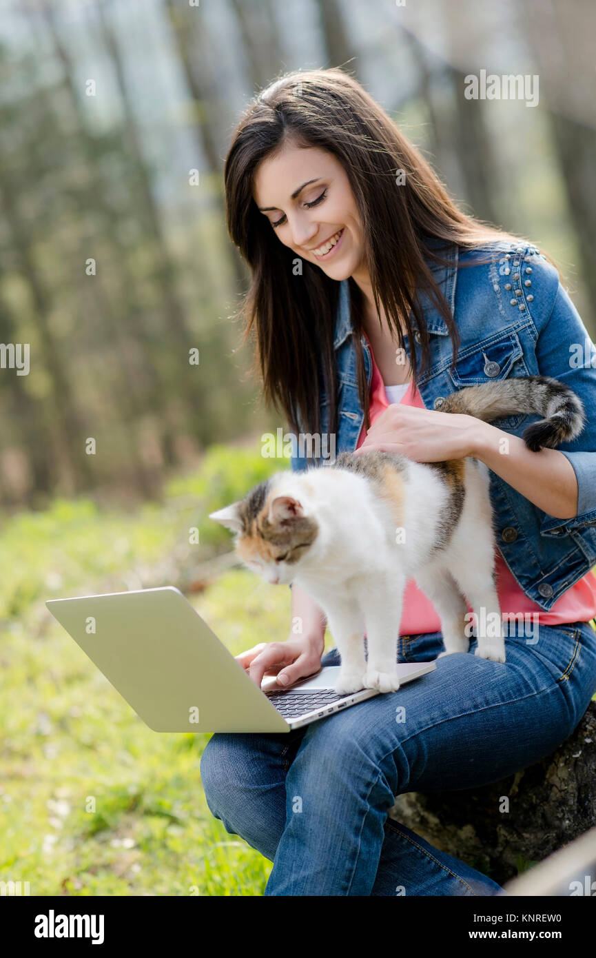 Junge Frau mit Katze sitzt mit Laptop in der Natur - woman with cat and laptop in nature Stock Photo