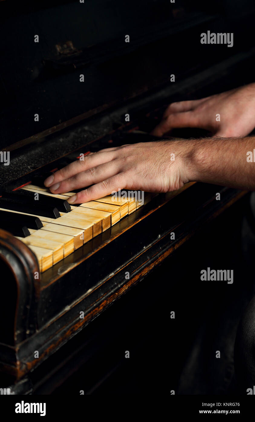 Old vintage classical black piano with male hand playing on it in