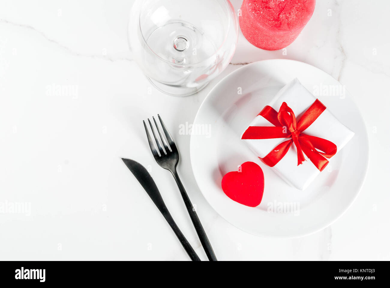 Valentine\'s day table setting with plate, fork, knife, gift box and ...